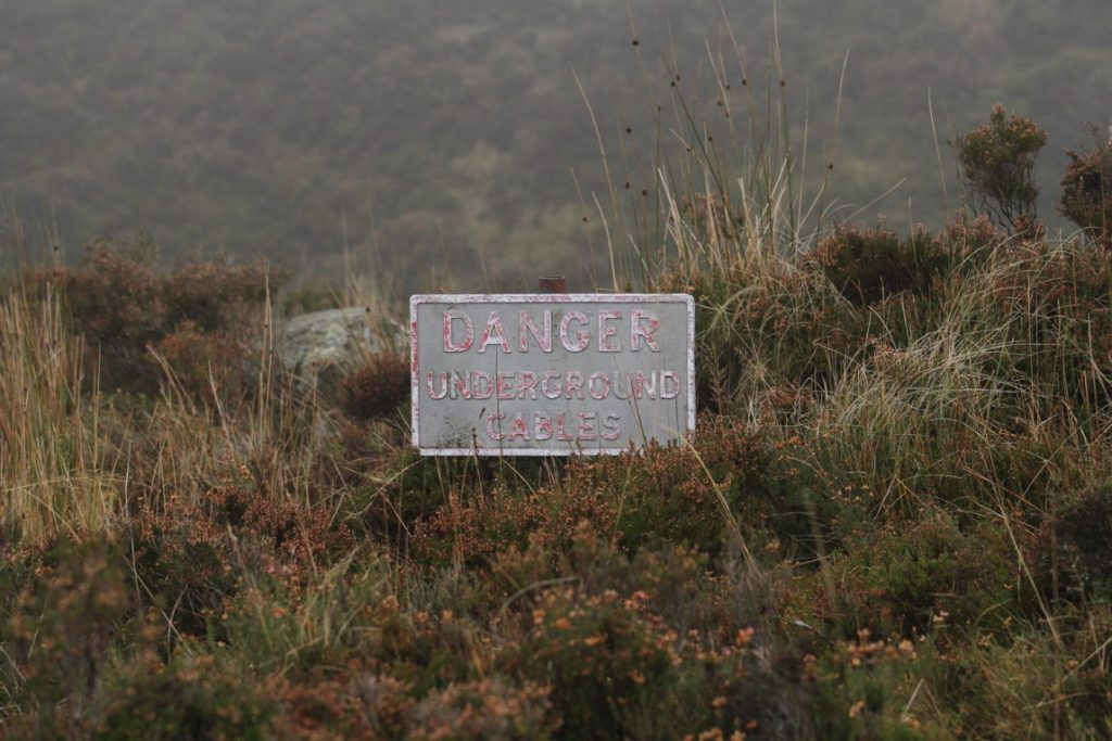 A photograph of a sign that reads Danger Underground Cables in faded lettering. The sign is old, and overgrowth of grass and shrubs is beginning to cover it up.