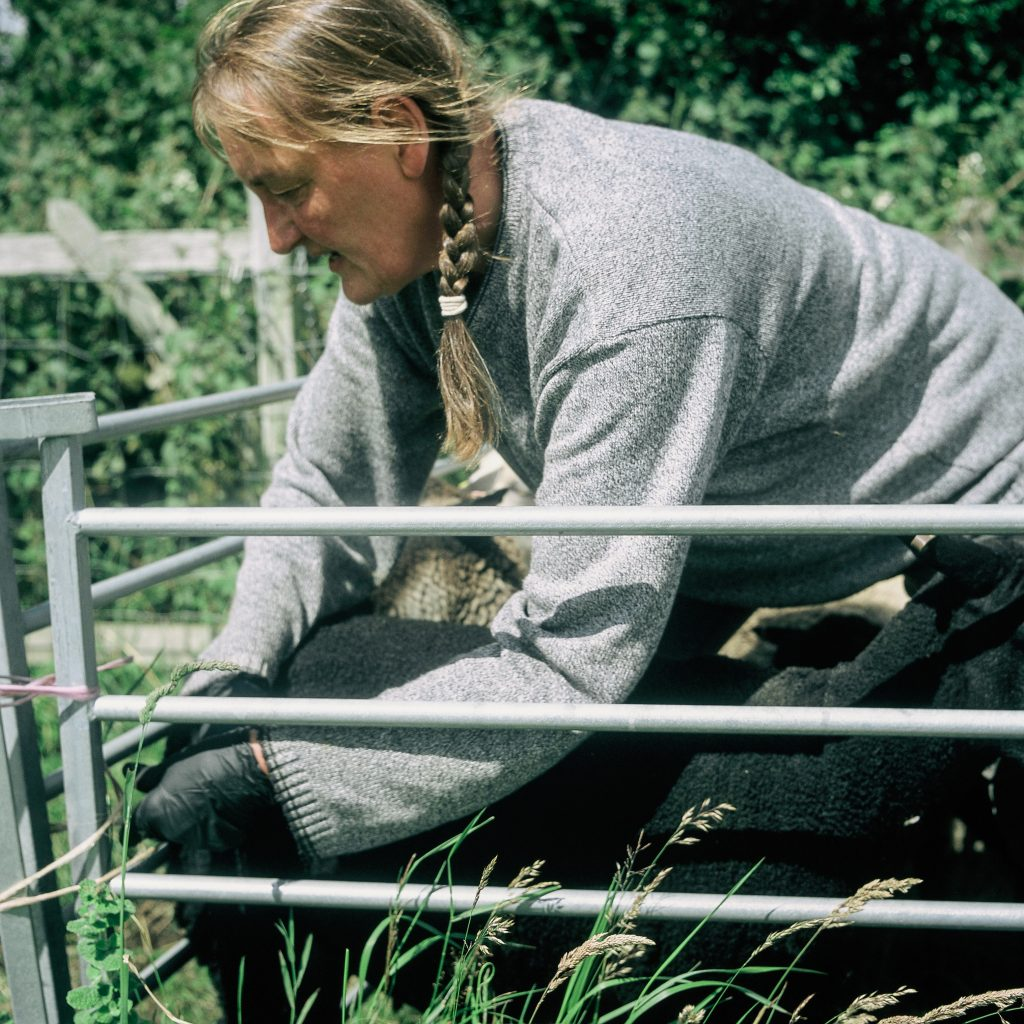 A female farmer is crouched down tying a metal gate to a metal pole