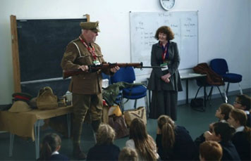Members of the Time Bandits standing in front of a class of school children. He is dressed as a WWI soldier holding a gun