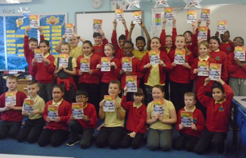 School chidren from 1 of the 5 Primary schools holding up their own class alphabet books