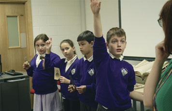 School children handling items from the Thomas Baker Brown archive and a child at the front holding up his hand to answer a question