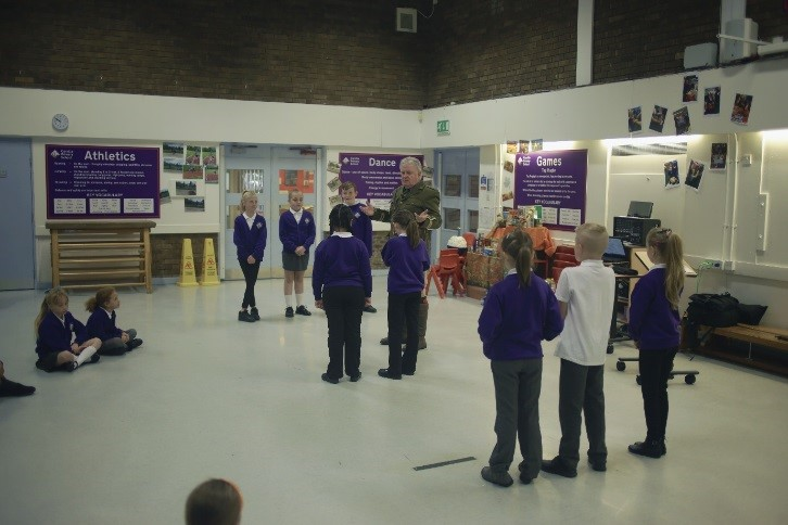 Schools children lining up in twos and bring taught a WWI drill by one of the Time Bandits
