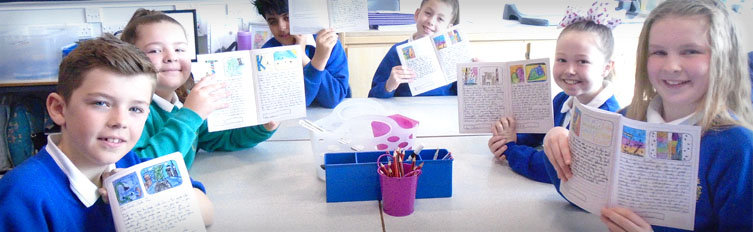 Header image showing a group of 6 primary school pupils holding up their alphabet books