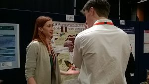 Photo of Chess Ridley discussing her poster with another delegate