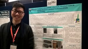 Issac Goh standing in front of poster at the conference