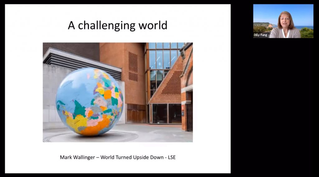 A challenging world powerpoint slice, with a small image  of the speaker Dilly Fung in Zoom