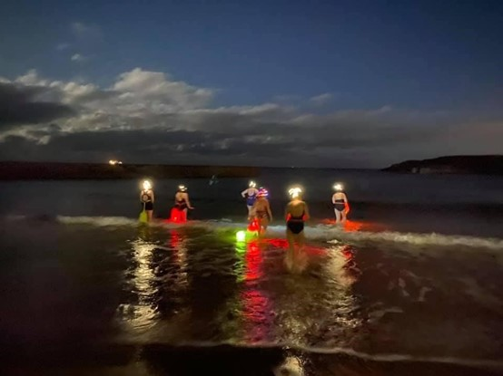 Six women entering the sea at dusk wearing neon colours and safety lights