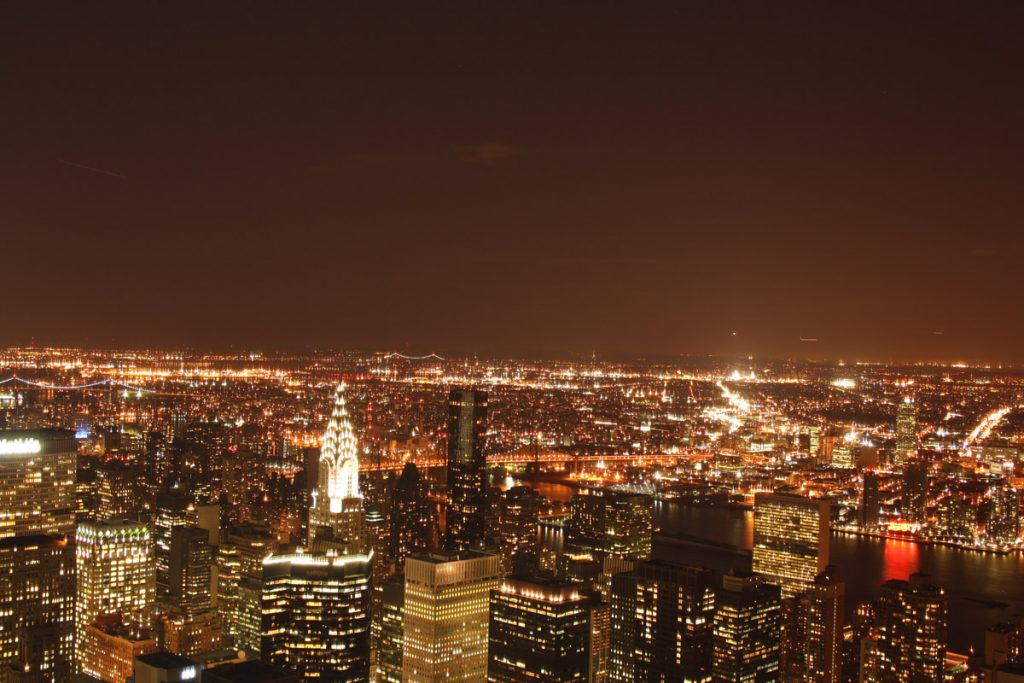 A photograph of New York City taken from a high building, lit up at night showing large skyscrapers with illuminated windows, out to distant suburbs and lower lying housing