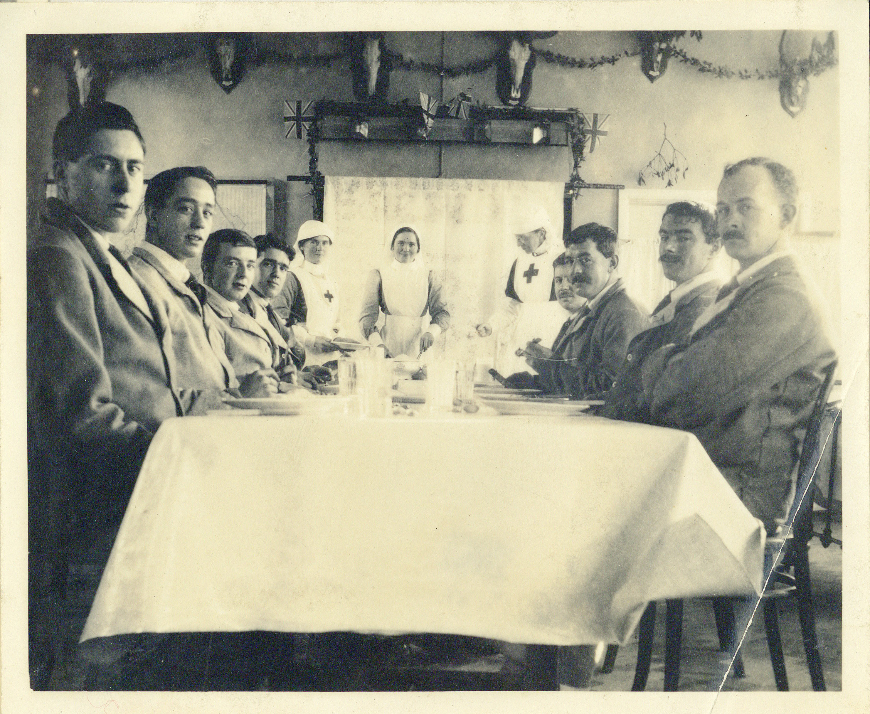 Photograph of soldiers and nurses around a table at the auxiliary Hospital at Rounton Grange, New Years Eve, 1916 (Charles Philips Trevelyan Archive, CPT/PA/6/)