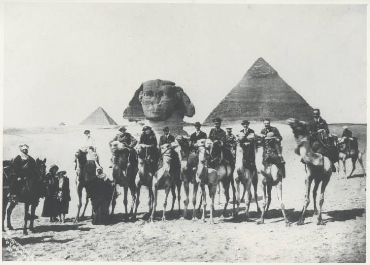 Photograph of Gertrude Bell and group, including Winston Churchill and T.E. Lawrence, on camels involved in the 1921 Cairo Conference