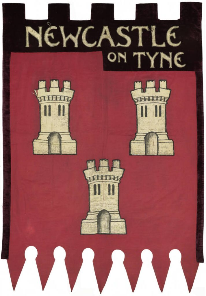 Suffragette Marching banner with 'Newcastle on Tyne' across the top and 3 castles in a reddish background