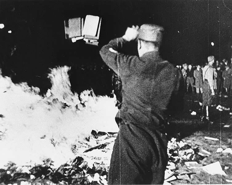 """Photograph of a member of the SA throws confiscated books into the bonfire during the public burning of """"un-German"""" books on the Opernplatz in Berlin."""
