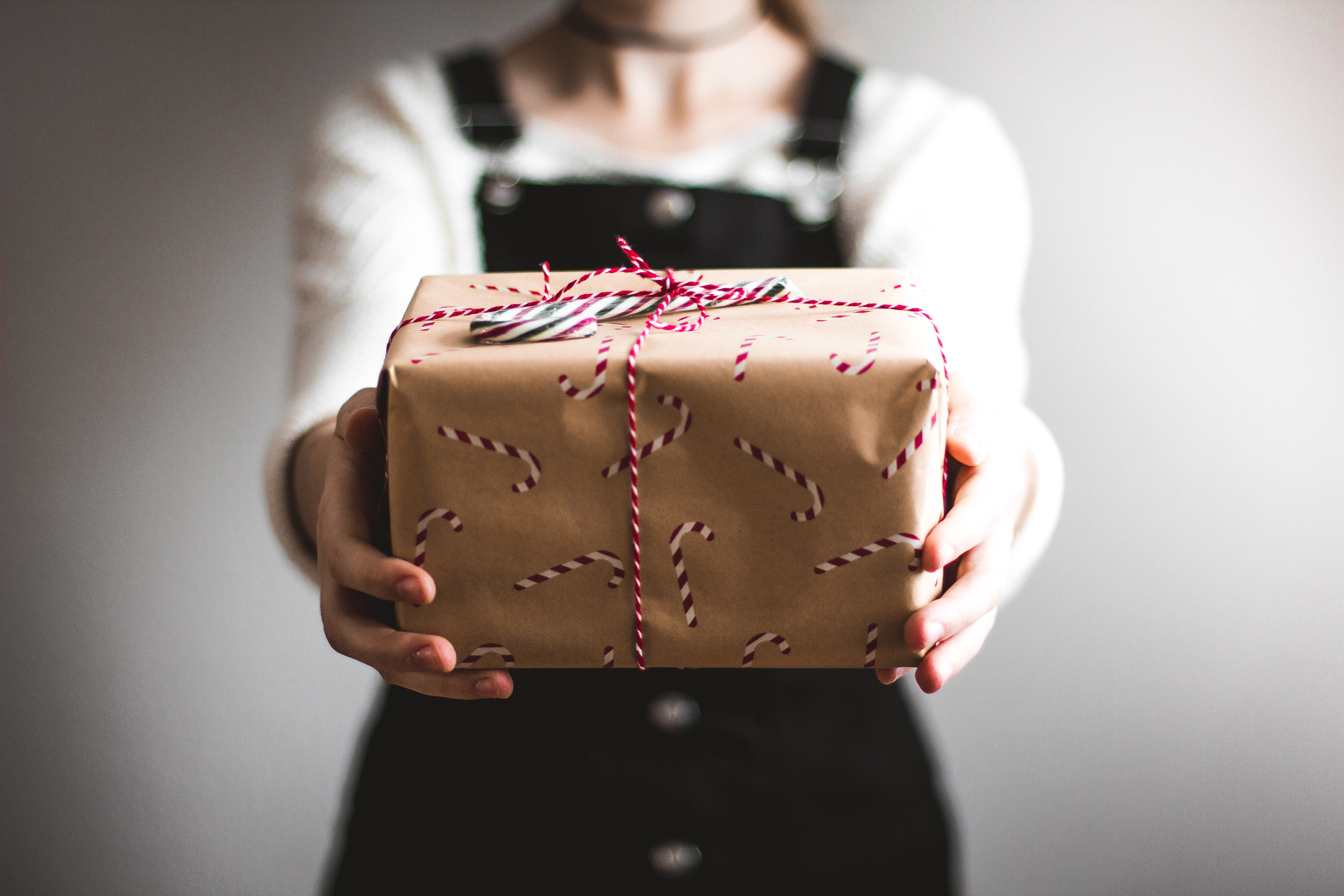 Person holding a gift box wrapped in brown paper with candy stripe ribbon.