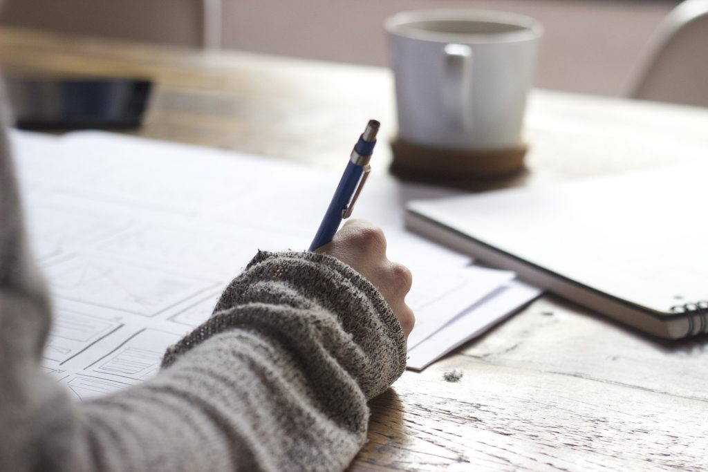 A person writing at a desk