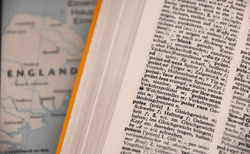 A portion of a map of England can be seen beneath a foreign language dictionary.