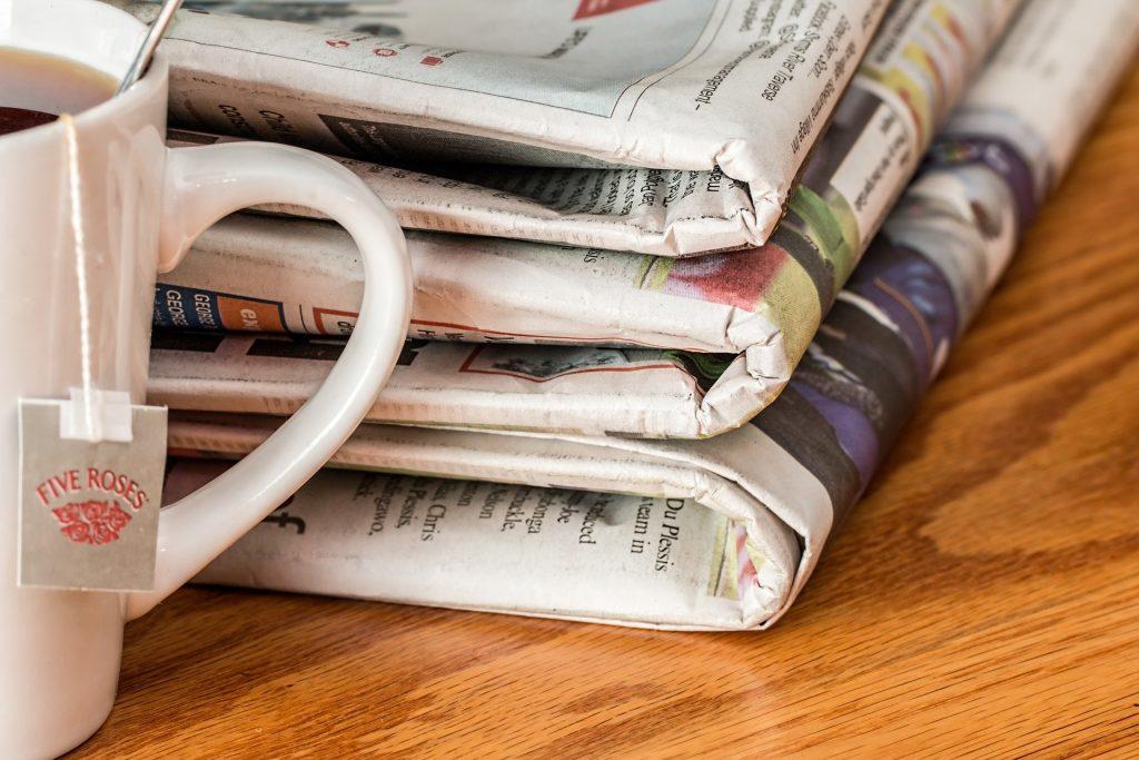 Three newspapers piled on a desk next to a mug of tea.