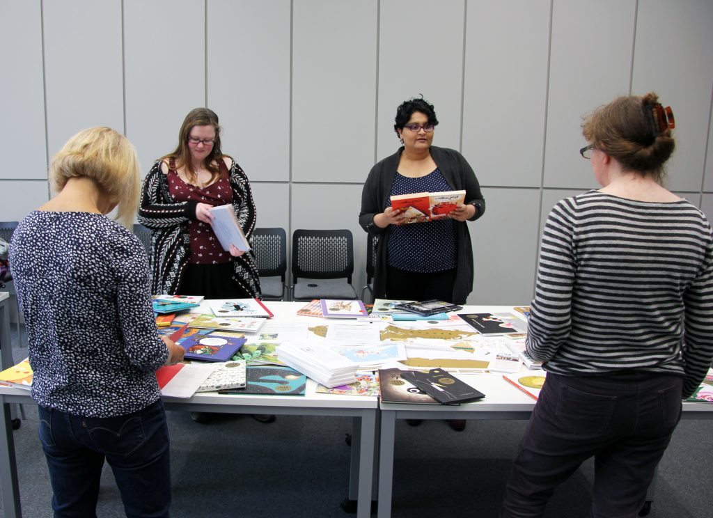 Staff and students from the Children's Literature Unit Graduate Group discuss the IBBY Honour collection. Image: Newcastle University