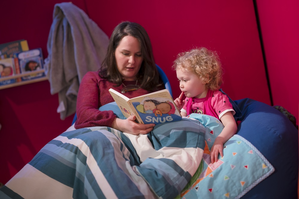 A parent reads with a young child at Seven Stories. Image: Seven Stories, The National Centre for Children's Books, photography by Richard Kenworthy